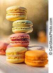 French macarons in the summer evening in the garden. Delicious sweet airy colored French pastries. Shallow depth of field