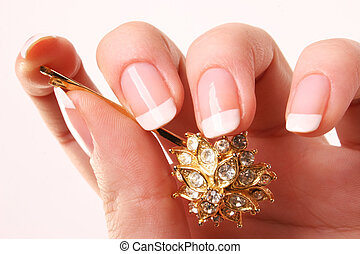Woman's hand with French manicure and glitter hairpin