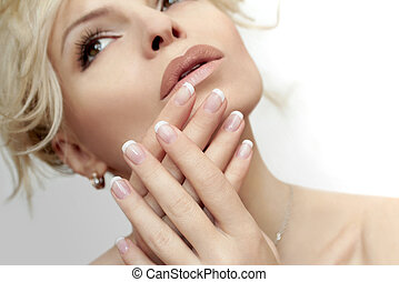 French manicure. - Short French manicure on hands of a young...