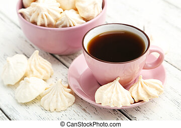 French meringue cookies with cup of coffee on white wooden background