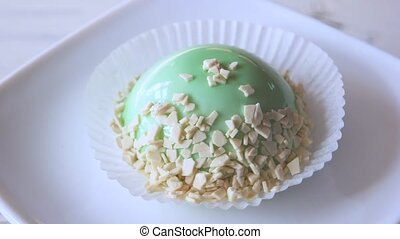 French mousse covered with mint glaze. Yummy dessert with mirror glaze decorated with white chocolate. Modern French pastry.