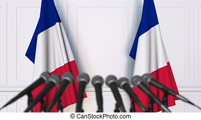 French official press conference. Flags of France and...
