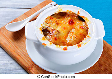 french onion gratin soup in a white pot, close-up