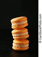 French orange macarons on black background