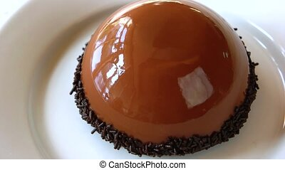 French pastry with chocolate glaze. French mousse cake with shiny cocoa glaze on white plate. Modern european cake pastry.