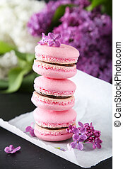 French pink macarons with lilac flowers on black background