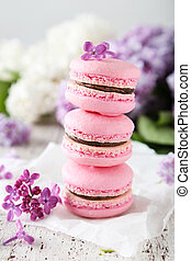 French pink macarons with lilac flowers on white wooden backgrou