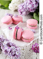 French pink macarons with lilac flowers on white wooden background