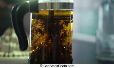 French press with hot tea in light slowmotion. Beautiful tea...