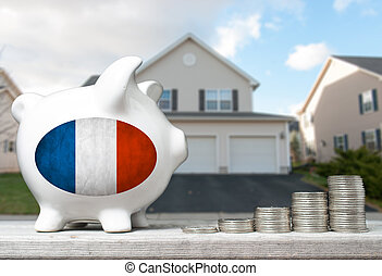 French real estate investment concept with piggy bank, stacks of coins and house in the background