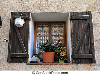 french rustic window with old wood shutters in stone rural...