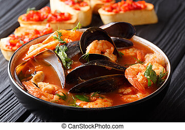 French seafood bouillabaisse soup closeup in a bowl served with toast. horizontal