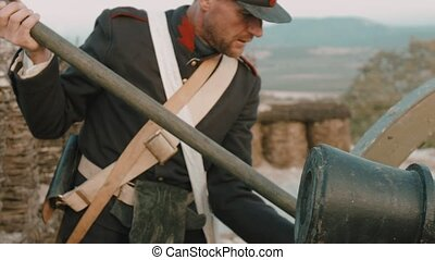 French soldier prepares a military cannon for battle