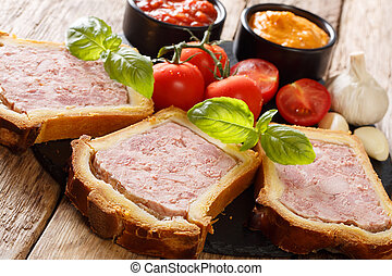 French terrine, pate in a brioche served with vegetables and sauces close-up on the table. horizontal, rustic
