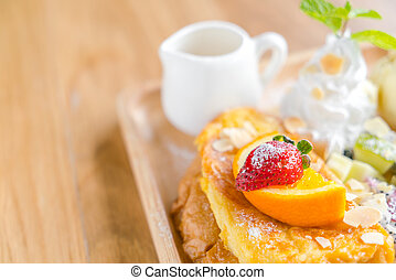 French toast with powdered sugar and a strawberry on wood table .