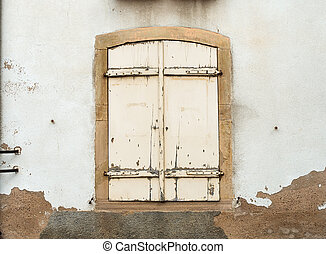 French window with closed old medieval wooden shutters.