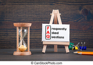 frequently asked questions. Sandglass, hourglass or egg timer on wooden table