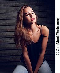 fresco, contemporâneo, mulher jovem, com, cabelo longo, sentando, em, calças brim, ligado, rua, parede, experiência., toned, retrato