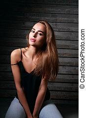 fresco, contemporâneo, mulher jovem, com, cabelo longo, sentando, em, calças brim, ligado, rua, parede, fundo