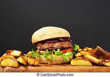 Fresh american burger with fried potatoes on wooden board. Closeup.