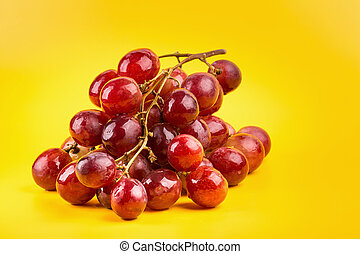 fresh and delicious red grapes isolated on yellow background