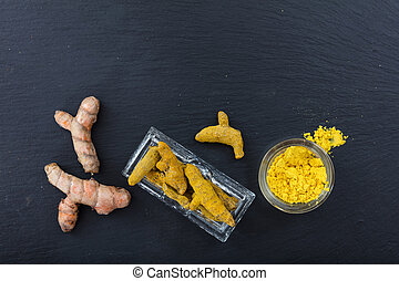 Fresh and dried turmeric roots and powder on black background. Top view, copy space