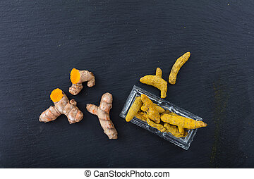 Fresh and dried turmeric roots on black background. Top view, copy space
