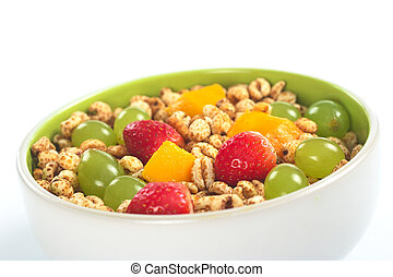 Fresh and healthy breakfast: Fruit salad out of mango, strawberry and white grape with puffed wheat cereal (Selective Focus, Focus on the middle of the bowl)