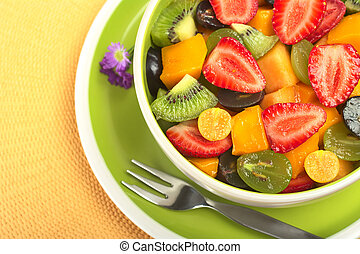 Fresh and healthy fruit salad with strawberry, kiwi, grape, mango and physalis in a bowl with fork and small blue flowers photographed from above (Selective Focus, Focus from the front to the middle o