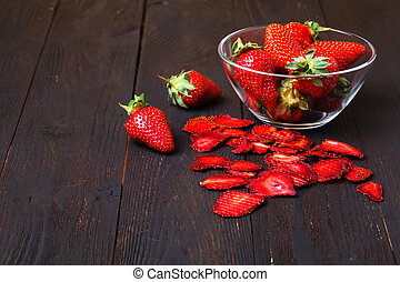Fresh and homemade dried strawberries on wooden table