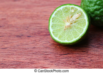 Fresh and organic kaffir limes on wooden texture
