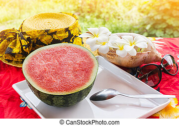 Fresh and red watermelon fruit and spoon on white tray on table with yellow summer hat ,sunglasses and plumeria or frangipani flowers and sea conch shell in background,