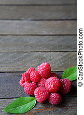 fresh and ripe raspberries on a wooden table