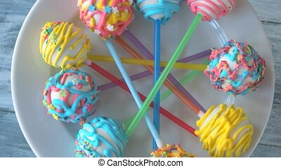 Fresh and tasty cake pops on plate. Glaze with sprinkles. Beautiful design of sweets.