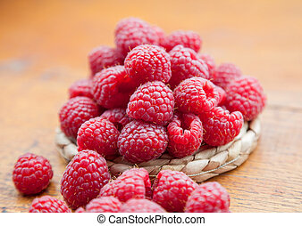 Fresh and tasty raspberries on a wooden table