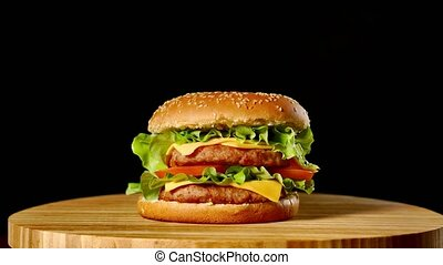 Fresh appetizing hamburger rotating on black background....