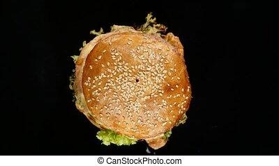 Fresh appetizing hamburger rotating on black background....