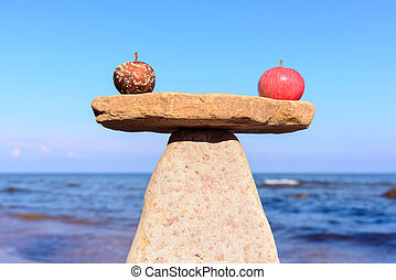 Fresh apple and rotten in balance on stones