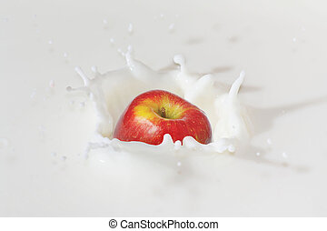Fresh apple falling into the milk with a splash closeup