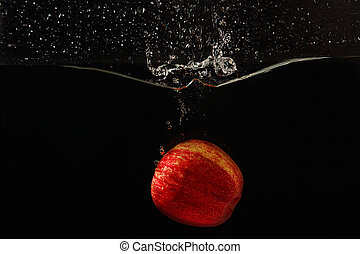 Fresh apple falling into the water with a splash on a black background closeup