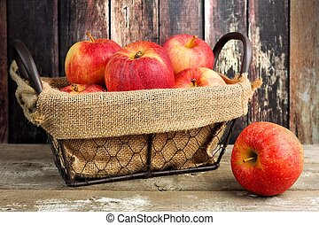 Fresh apples in a vintage wire basket with burlap against rustic wood