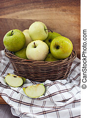 Fresh apples in basket on table
