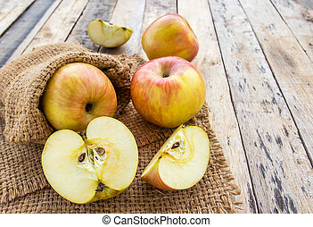Fresh apples in burlap sack on wooden table background