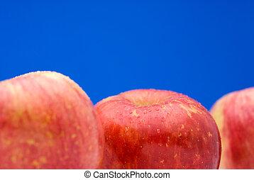 Fresh apples on bright Blue