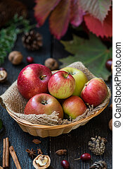 Fresh apples with autumn leaves on wooden table