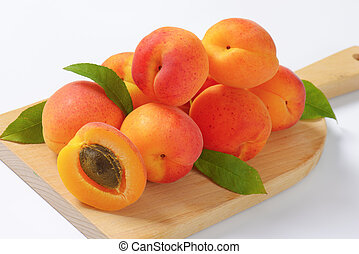 Fresh apricots - Heap of ripe apricots on wooden cutting...