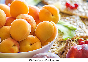 Fresh apricots in a white dish and other fruits on the kitchen table. Healthy lifestyle