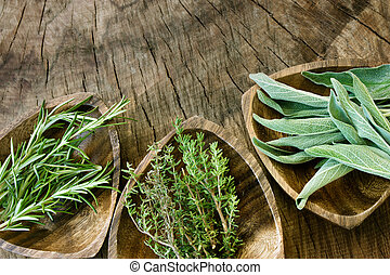 Fresh aromatic herbs on old wooden background