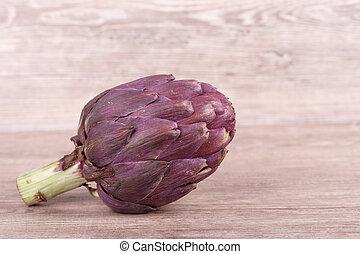 fresh exotic purple artichoke on wooden background