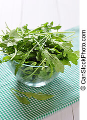 Fresh arugula leaves in glass bowl on a white wooden...
